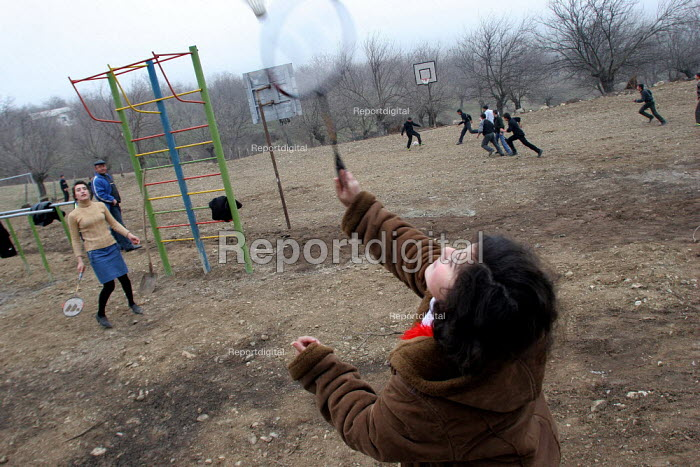 Teenagers play badminton in Drakhtik, Nagorno Karabakh, Azerbaidjan, March 2005. The region, although officially located within Azerbaidjan, is being occupied by Armenia and has became a de facto Republic strongly linked with Armenia. The conflict, considered is still pending and the status of Nagorno Karabakh is unresolved. - Boris Heger - 2005-03-04