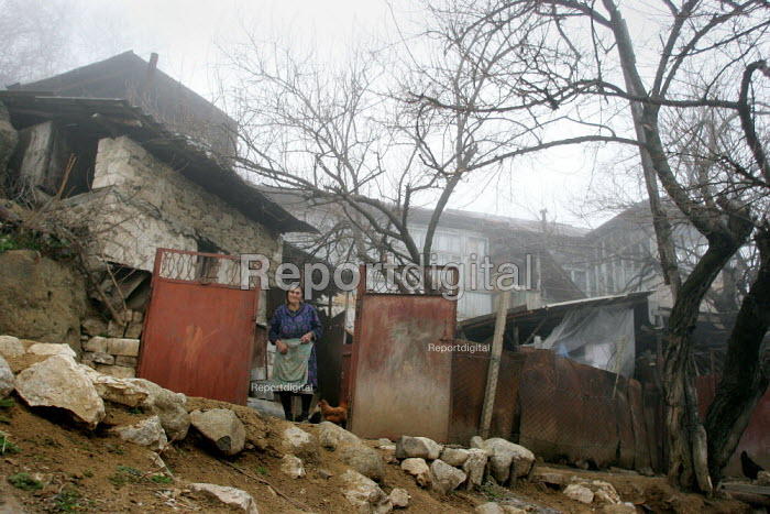 House and woman, Azokh, Nagorno Karabakh, Azerbaidjan, March 2005. The region, although officially located within Azerbaidjan, is being occupied by Armenia and has became a de facto Republic strongly linked with Armenia. The conflict, considered is still pending and the status of Nagorno Karabakh is unresolved. - Boris Heger - 2005-03-04