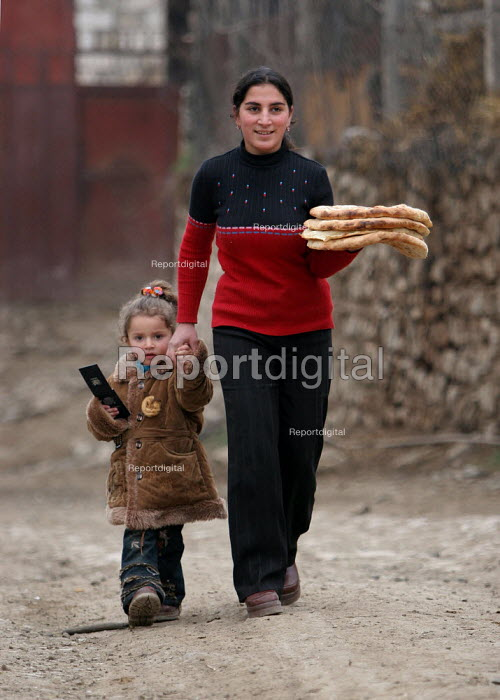 A girl carries bread with her sister, Azokh, Nagorno Karabakh, Azerbaidjan, March 2005. The region, although officially located within Azerbaidjan, is being occupied by Armenia and has became a de facto Republic strongly linked with Armenia. The conflict, considered is still pending and the status of Nagorno Karabakh is unresolved. - Boris Heger - 2005-03-04