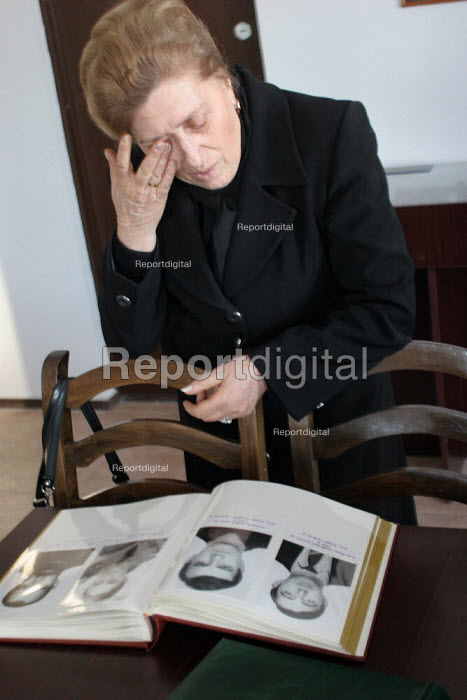 A member of a war missings association visit a mausoleum dedicated to their relatives at the war section of the National Cemetery. Woman crying as she looks at a book with the photographs of her son, Tbilisi, Georgia, March 2005 - Boris Heger - 2005-03-07