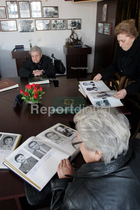 Members of a war missings association visit a mausoleum dedicated to their relatives at the war section of the National Cemetery and review books with the photographs of soldiers killed in the separatist war over the province of Abkhazia, Tbilisi, Georgia, March 2005. - Boris Heger - 2005-03-07