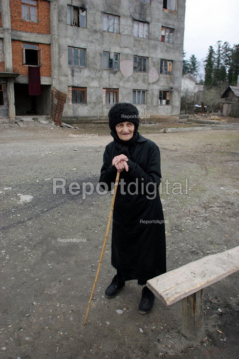 An old displaced person stands in front of a delapitated residential block transformed into a center for Georgians who used to live in Abkhazia, Zugdidi, Georgia, March 2005. The region of Abkhazia, officially still part of Georgia, conducted a separatist war with Georgia for years at the fall of the USSR and became a de facto republic supported by Russia. Its status is not officially resolved. - Boris Heger - 2005-03-08