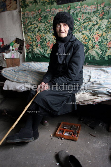 An old lady in her room, in a delapitated residential block transformed into a displaced persons center for Georgians who used to live in Abkhazia, Zugdidi, Georgia, March 2005. The region of Abkhazia, officially still part of Georgia, conducted a separatist war with Georgia for years at the fall of the USSR and became a de facto republic supported by Russia. Its status is not officially resolved. - Boris Heger - 2005-03-08