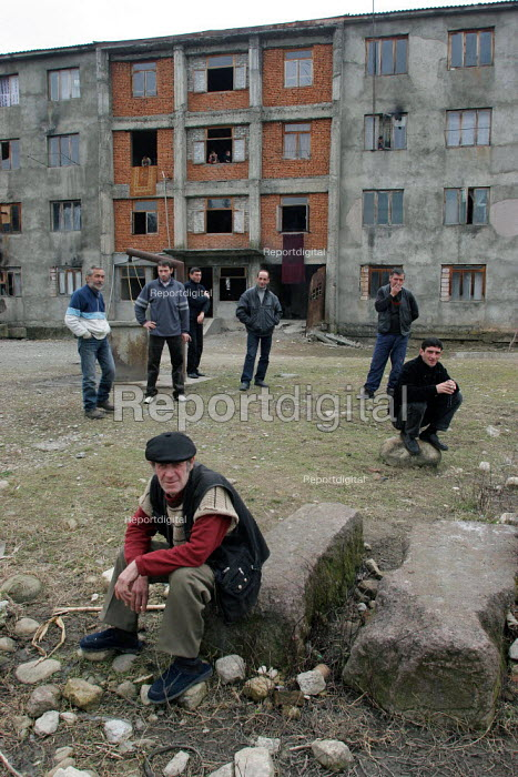 Displaced jobless men in front of a delapitated residential block transformed into a center for Georgians who used to live in Abkhazia, Zugdidi, Georgia, March 2005. The region of Abkhazia, officially still part of Georgia, conducted a separatist war with Georgia for years and became a de facto republic supported by Russia. Its status is not officially resolved. - Boris Heger - 2005-03-08