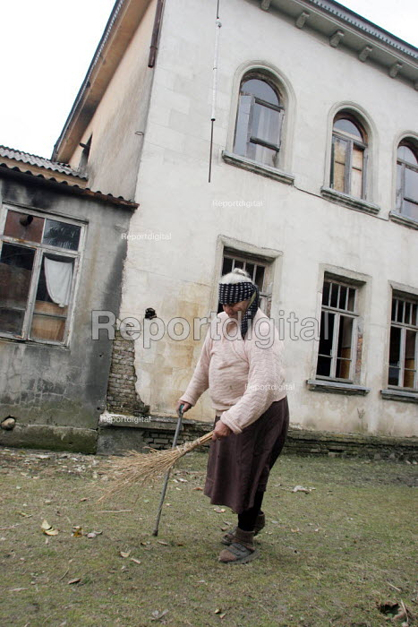 A man cleans the surroundings of an old delapitated residential block transformed into a displaced persons center for Georgians who used to live in Abkhazia, Zugdidi, Georgia, March 2005. The region of Abkhazia, officially still part of Georgia, conducted a separatist war with Georgia for years at the fall of the USSR and became a de facto republic supported by Russia. Its status is not officially resolved. - Boris Heger - 2005-03-08