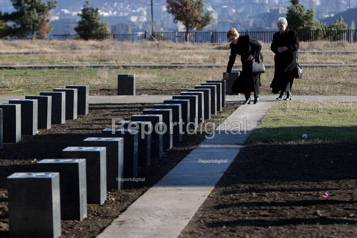 Members of a war missings association come out of a mausoleum dedicated to their relatives at the war section of the National Cemetery after paying their respects, Tbilisi, Georgia, March 2005. The region of Abkhazia, officially still part of Georgia, conducted a separatist war with Georgia for years at the fall of the USSR and became a de facto republic supported by Russia. Its status is not yet resolved. - Boris Heger - 2005-03-07