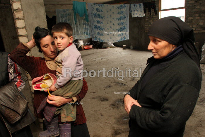 A family in a delapitated residential block transformed into a displaced persons center for Georgians who used to live in Abkhazia, Zugdidi, Georgia, March 2005. The region of Abkhazia, officially still part of Georgia, conducted a separatist war with Georgia for years at the fall of the USSR and became a de facto republic supported by Russia. Its status is not officially resolved. - Boris Heger - 2005-03-08