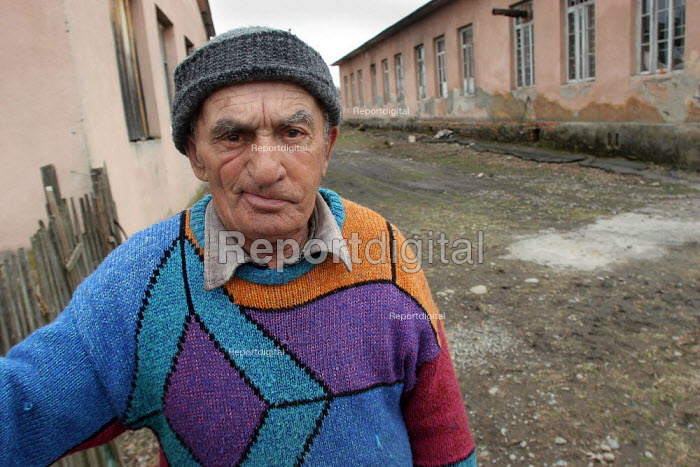 A man stands in front of a delapitated residential block transformed into a displaced persons center for Georgians who used to live in Abkhazia, Zugdidi, Georgia, March 2005. The region of Abkhazia, officially still part of Georgia, conducted a separatist war with Georgia for years at the fall of the USSR and became a de facto republic supported by Russia. Its status is not officially resolved. - Boris Heger - 2005-03-08