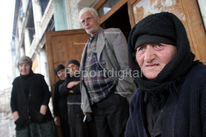 Old people stand in front of an old former official building transformed into a displaced persons center for Georgians who used to live in Abkhazia, Kutaisi, Georgia, March 2005. The region of Abkhazia, officially still part of Georgia, conducted a separatist war with Georgia for years at the fall of the USSR and became a de facto republic supported by Russia. Its status is not officially resolved. - Boris Heger - 2005-03-10