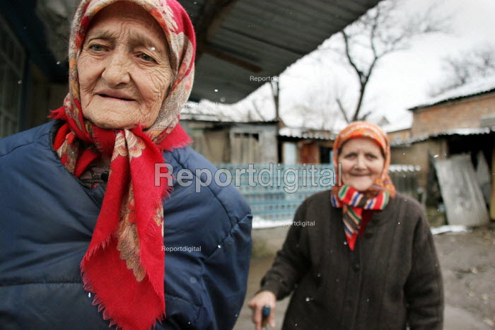 Two old sisters who lost their husbands during the war, in front of their home, Grozny, Chechnya, March 2005. - Boris Heger - 2005-03-23