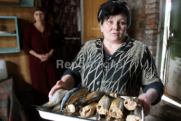 A lady displays dry fish she sells in order to make money for her family to survive, Grozny, Chechnya, March 2005. - Boris Heger - 2005-03-23