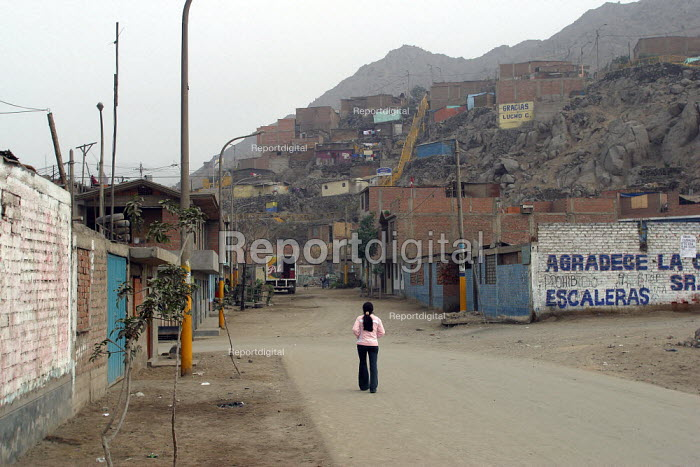 Lone girl walking down the street of a slum in the citys outskirts. Lima, Peru, September 2004. - Boris Heger - 2004-08-29