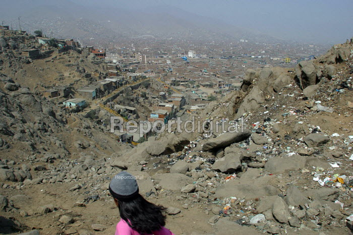 A girl passes by on a hill overlooking the slum where she lives, Lima, Peru, September 2004. - Boris Heger - 2004-08-29
