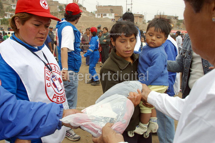 The poorest families of a slum receive food parcels from the Peruvian Red Cross, Lima, Peru, September 2004. - Boris Heger - 2004-08-29