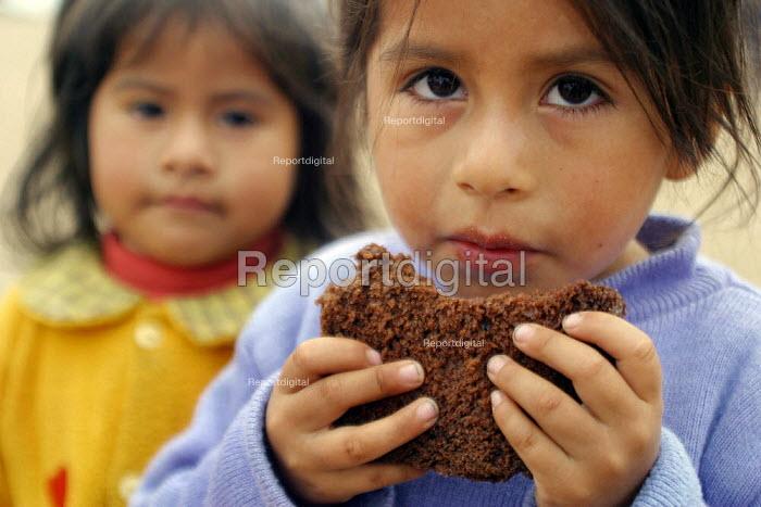 Girls eating a piece of bread, Lima, Peru, September 2004. - Boris Heger - 2004-08-29