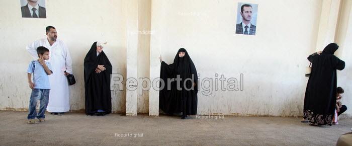 Arriving Iraqi refugee women waiting under posters of Syrian President Bashar Al-Assad ahead of security checks on the Syrian side of the border. Al Tanf Iraq-Syria border. - Morris Bernard - 2007-08-24