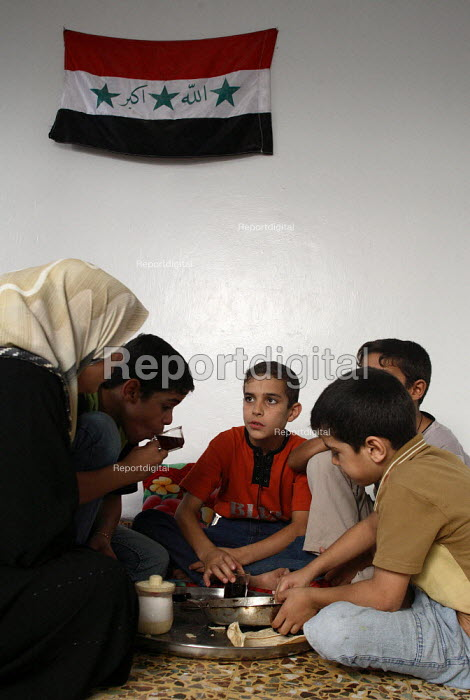 Iraqi refugee children in their main room at home eat a simple meal with their mother under an iraqi flag, in this area densely populated with Iraqi refugees. There is an estimated 1.4 million Iraqis who sought refuge in Syria due to the ongoing violence in their country. Saida Zeinab, Damas, Syria. - Morris Bernard - 2007-08-30