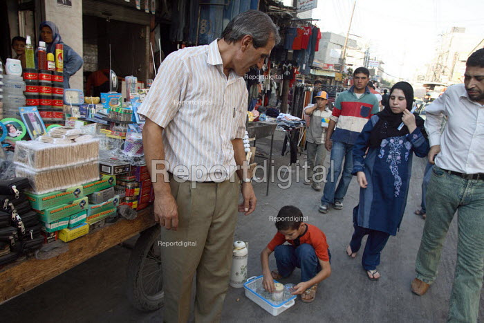 A refugee child selling tea in the street to support his family serves a customer passes by in this area densely populated with Iraqi refugees. There is an estimated 1.4 million Iraqis who sought refuge in Syria due to the ongoing violence in their country. Saida Zeinab, Damas, Syria. - Morris Bernard - 2007-08-30
