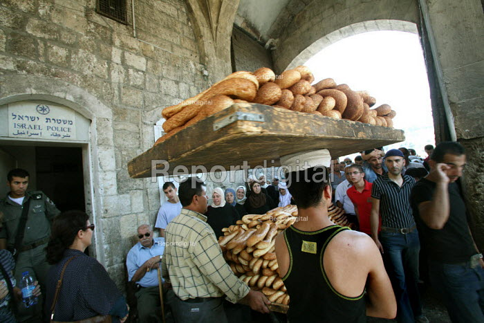 A policeman at an Israeli police post at the old city entrance of the Lion gate watches bread merchants trying to exit the walls as thousands of Muslim worshippers head to pray at the Al-Aqsa Mosque, East Jerusalem, September 14, 2007, for the first Friday of Ramadan of the Islamic year 1428, as Israel tightened security measures around the Holy City. - Boris Heger - 2007-09-14