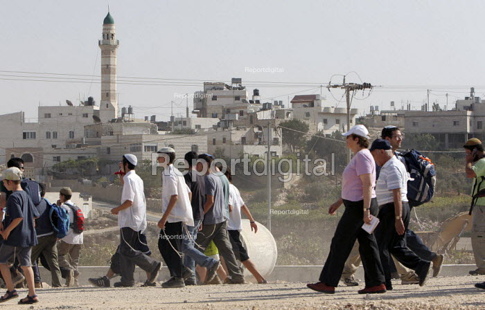 Jewish settlers pass in front of a mosque, while marching from the West Bank settlement of Efrat toward a hill called Eitam, near Bethleem, where they want to establish an outpost settlement. Israeli settlers and right-wing groups announced that they would attempt to create five new outpost settlements, not authorized by Israel. - Morris Bernard - 2007-09-30