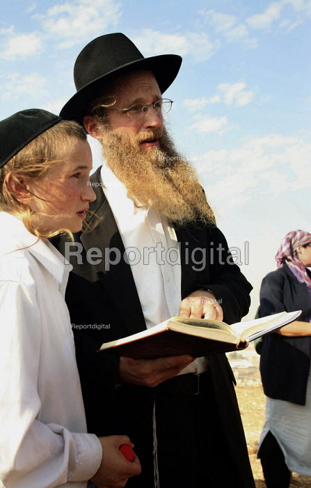 A Jewish Orthodox settler and his son pray and read the sacred Torah book on a hill called Eitam, near Bethleem, where they want to establish an outpost settlement. Israeli settlers and rightwing groups announced that they would attempt to create five new outpost settlements, not authorized by Israel. - Morris Bernard - 2007-09-30