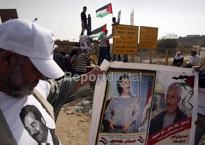 Relatives of released Palestinian prisoners from Israeli jails display portraits of Saddam Hussein and wave flags before the bus carrying them arrives. Fifty-seven Palestinian prisoners arrived to a heros welcome in the West Bank after Israel released them in a Ramadan goodwill gesture to president Mahmud Abbas. - Morris Bernard - 2007-10-01