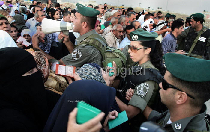 Palestinian Muslim worshippers show id cards at an Israeli army checkpoint by the barrier that separates the West Bank and Jerusalem. They are trying to reach Jerusalems Al Aqsa Mosque, which is between the West Bank city of Ramallah and Jerusalem, for Lilat al-Qader. According to Muslim tradition The Koran was revealed to the Prophet Mohammed during the night of Lilat al-Qader. - Morris Bernard - 2007-10-08