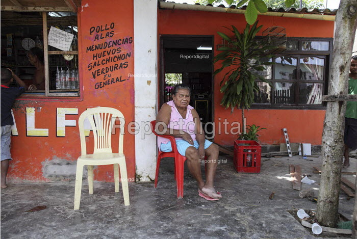 An internally displaced woman sitting in front of her house next to a shop - a general store selling food- in the poor suburb of Pozos Azules, Cartagena. - Boris Heger - 2010-11-10