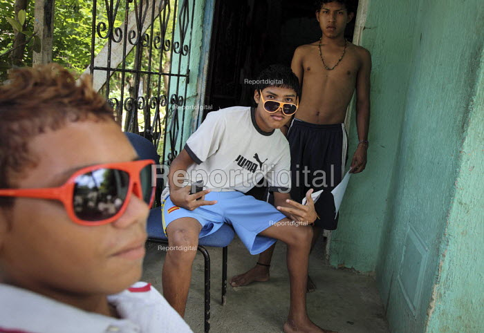 Internally displaced boys in their sunglasses playing at being gang members in front of their house in the poor suburb of Pozos Azule, Cartagena. - Boris Heger - 2010-11-10