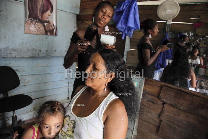An internally displaced woman who just started a small hairdressers business attending to a client in the poor suburb of Pozos Azules, Cartagena. - Boris Heger - 2010-11-10