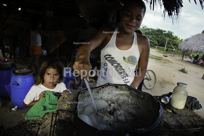 An internally displaced indigenous woman preparing some food with her child in her shelter on the outskirts of the city, San Jose del Guaviare, Colombia. - Boris Heger - 2011-01-17