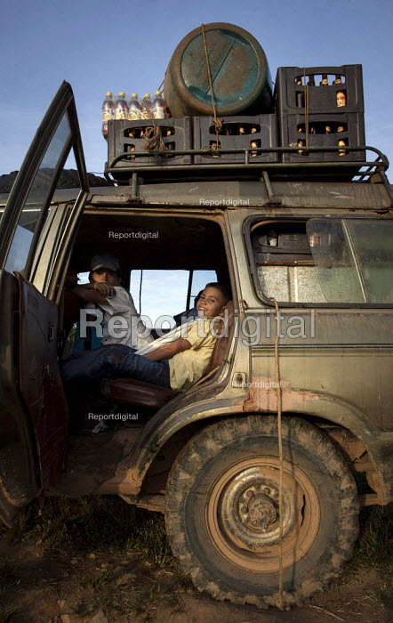 A boy sitting in an old 4x4 Land Cruiser, travel is often dangerous here, and roads are in bad condition. San Jose del Guaviare, Colombia. - Boris Heger - 2011-01-19