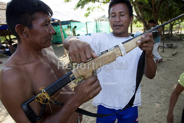 Two internally displaced indigenous men playing with a handmade gun outside their shelter on the outskirts of the city, San Jose del Guaviare, Colombia. - Boris Heger - 2011-01-20