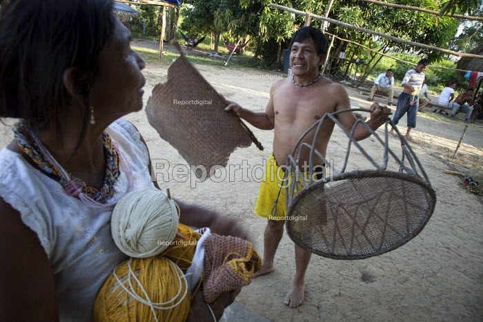Internally displaced indigenous people moving their handicrafts into their shelter. San Jose del Guaviare, Colombia. - Boris Heger - 2011-01-20