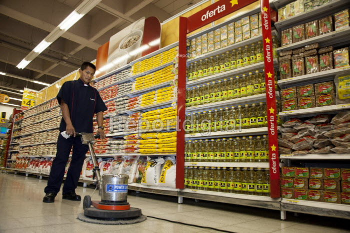 An internally displaced indigenous man working as a cleaner in a modern supermarket after having spent his entire life in the jungle. Villavicencio, Colombia. - Boris Heger - 2011-01-22