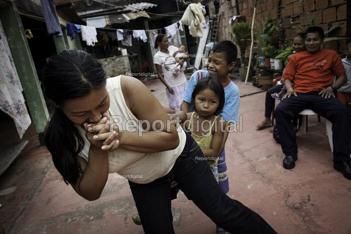 A mother keeping her children up with traditional customs by teaching them indigenous games and traditions. An internally displaced indigenous family in a poor neighbourhood in Villavicencio, Colombia. - Boris Heger - 2011-01-22
