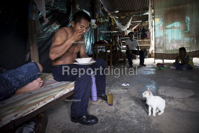 An internally displaced indigenous man who works in a supermarket having a meal at home after a long day at work, watched by a kitten, in a poor neighbourhood in Villavicencio, Colombia. - Boris Heger - 2011-01-22