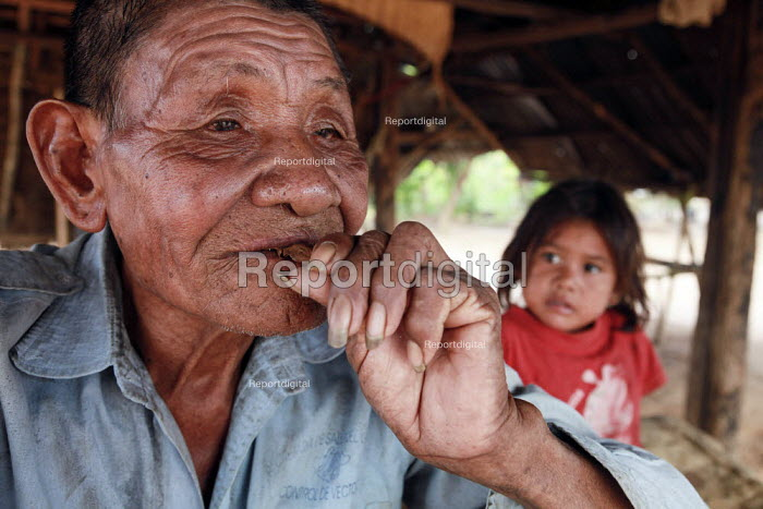 "An internally displaced indigenous shaman medicine man explaining to young members of his tribe the Ayahuasca root locally called ""Yage"". This hallucinogen drug is commonly used by some latin american tribes during ceremonies and for spiritual purposes. Meta, Colombia. - Boris Heger - 2011-01-17"