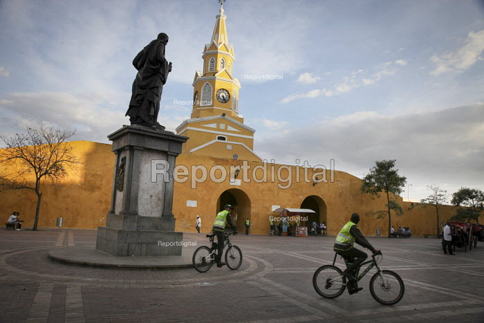 Police officers patrol with bikes on the streets of Cartagena, Colombia. At the colonial style El Reloj, or Clock Gate (built at the beginning of the 18th century by Juan de Herrera y Sotomayor) entrance to the walled city. The statue of Don Pedro de Heredia, Spanish conqueror and founder of the city of Cartagena de Indias (1533) - Boris Heger - 2011-02-20