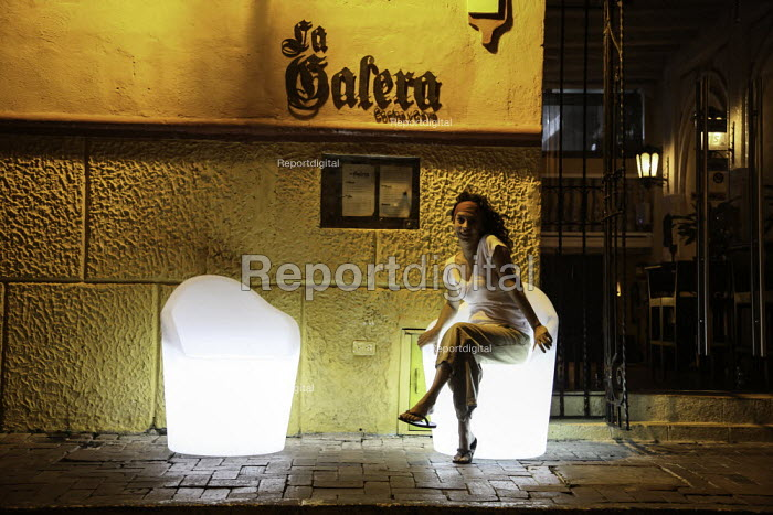 A girl waiting for her date on an illuminated seat at the entrance of a bar at night in Cartagena, Colombia. - Boris Heger - 2011-02-20