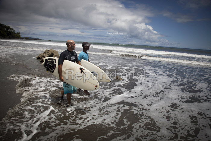Young surf champion PJ walking into the waves with his friend. Choco, Colombia. - Boris Heger - 2011-08-13