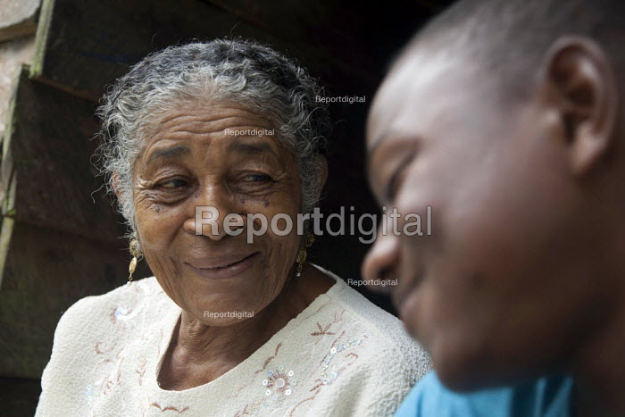 The young surf champion PJ sitting with his grandmother in front of her house, Choco, Colombia - Boris Heger - 2011-08-15