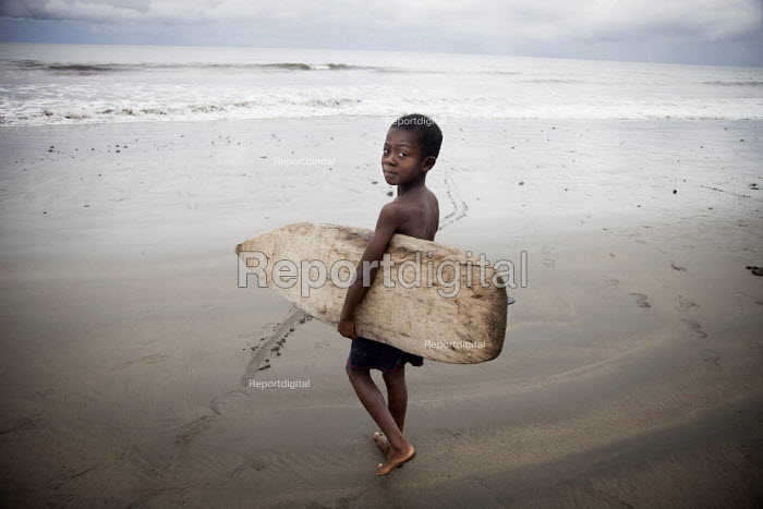 A young surfer heading to the water with a surfboard his older brother made for him from a balsa tree in the jungle. Choco, Colombia. - Boris Heger - 2011-08-14