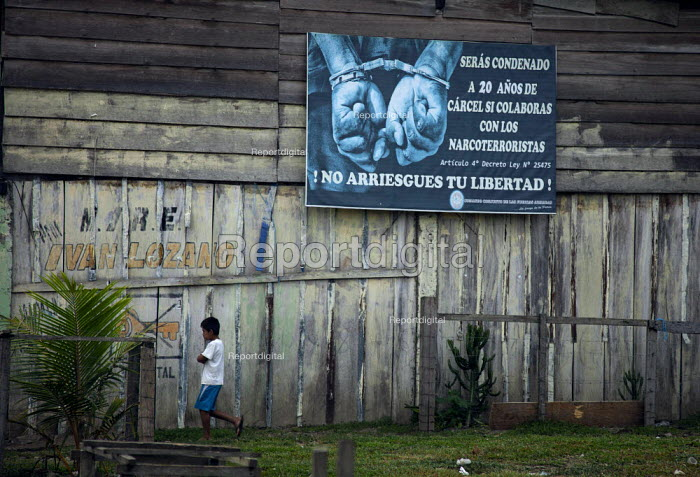 A child walks past a billboard warning that you will be condemed to 20 years in jail if you collaberate with Narcoterrorists. Do not risk your freedom. The remote jungle region of VRAE/ Ayacucho is increasingly invloved with coca trafficking and conflict with the maoist rebel group Shining Path. The last two years, Peru has surpassed Colombia in the amount of coca cultivation. - Boris Heger - 2012-10-13