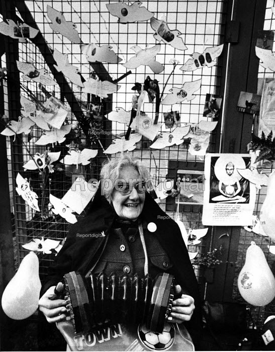 Veteran Peace campaigner Angela Gradwell playing her concertina USAF Greenham Common Cruise Missile base, 1982 - Bob Naylor - 1982-12-12