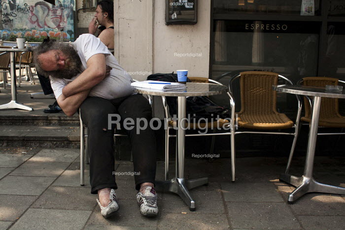 A rough sleeper rests and sleeps in the sun, Tottenham court road, London. - Connor Matheson - 2011-04-24