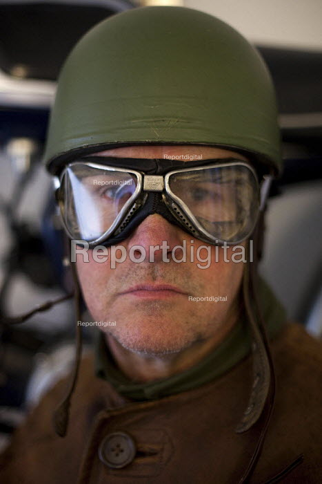 A Motorbike enthusiast poses in his world war two outfit (including aviator goggles) which he wears whilst riding his restored world war two motorbike. - Connor Matheson - 2012-04-07