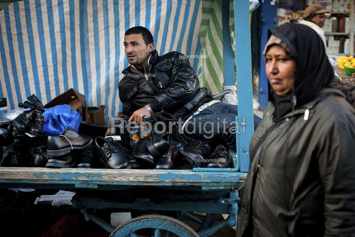 A shoe trader chats to another trader, East Street Market, Walworth, London. - Connor Matheson - 2012-11-29