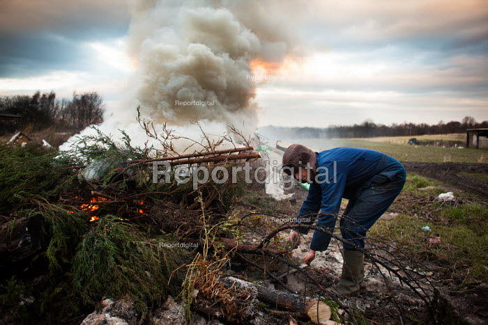 A young man burns waste in his back Garden farm/ scrapyard, Ryhill, Wakefield. Yorkshire - Connor Matheson - 2013-12-10