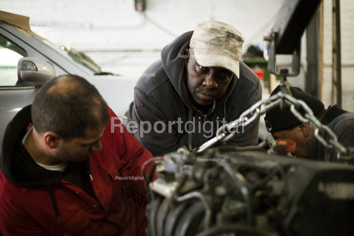 Three mechanics lift an engine in need of repair in a trade lockup Railway Arches Peckham. - Connor Matheson - 2014-05-24